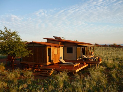 Bathed in orange light, the tents of the luxury Lodge Wolvedans blend with the environment: built on stilts with tents, each unit provides a luxurious immersion into the great outdoors. www.wolwedans-namibia.com